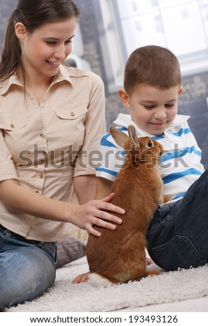 Young attractive mother and smiling son playing with cute pet bunny at home.