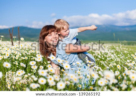 Young attractive mother playing with her son in field of daisies