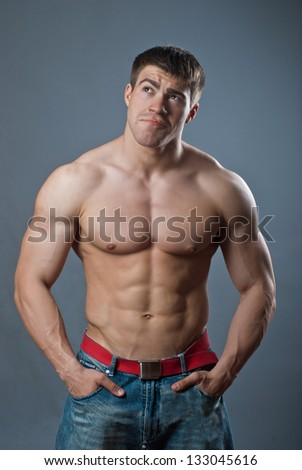 Young attractive muscular man on a black background, stripped to the waist - stock photo
