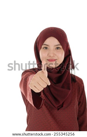Young attractive Muslim woman with scarf showing thumbs up - stock photo