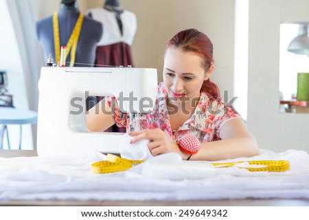 Young attractive needlewoman at studio working with sewing machine - stock photo