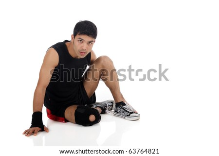Young attractive nepalese man athlete suffering from pain in the knee. White background. Studio shot.