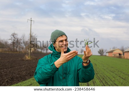 Young attractive peasant monitoring seedlings in the field in winter time - stock photo