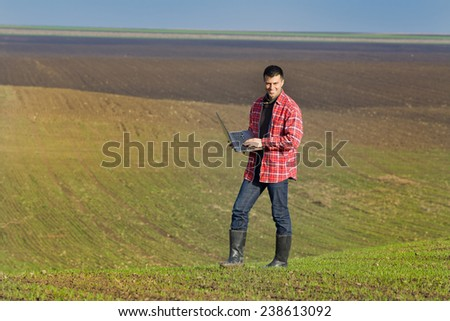Young attractive peasant with laptop monitoring seedlings in the field - stock photo