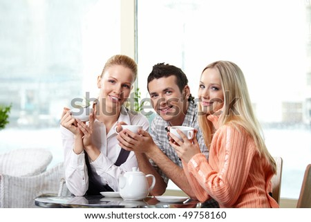 Young attractive people in cafe with cups - stock photo