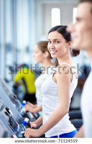 Young attractive people in the fitness club - stock photo