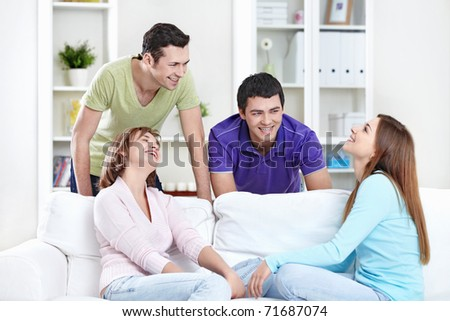 Young attractive people laugh in the apartment - stock photo