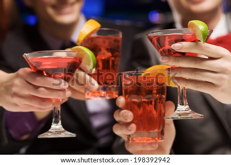 Young attractive people of four having cocktail party - stock photo