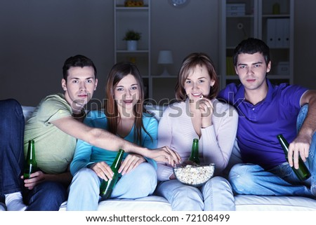 Young attractive people watch movies at home - stock photo