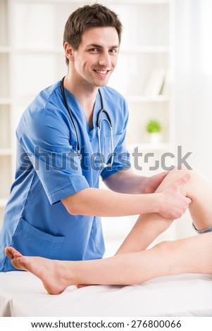 Young attractive physiotherapist massaging the  leg of female patient in a physio room. - stock photo