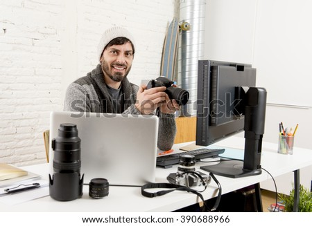 young attractive press photographer holding photographic camera viewing his work on editor office desk with laptop and computer monitor and photo lenses and gear smiling happy - stock photo