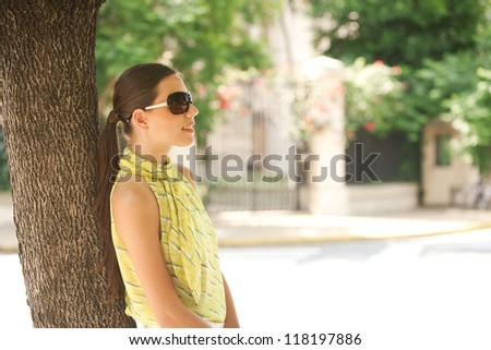 Young attractive professional businesswoman leaning on a tree trunk in the city, smiling. - stock photo