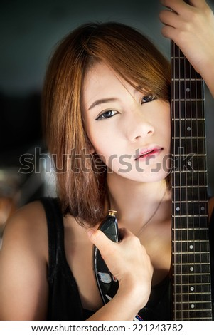 Young attractive rock girl and the electric guitar - stock photo