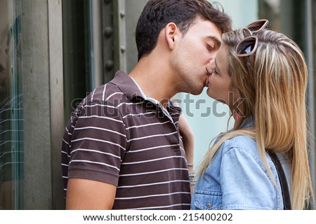 Young attractive romantic couple passionately kissing on holiday break in a vacation city, outdoors. Lifestyle and young people relationships. - stock photo