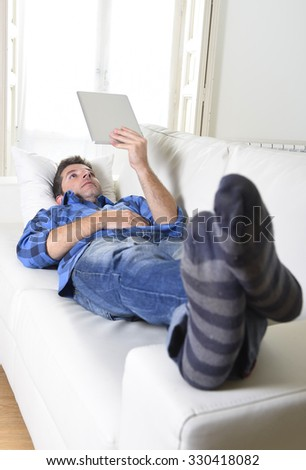 young attractive 30s man using digital tablet pad lying on couch at home living room networking looking relaxed and happy in portable technology and internet concept - stock photo
