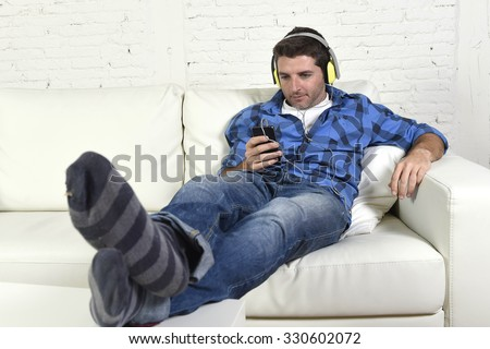 young attractive 20s or 30s man having fun alone lying on home couch listening to music with mobile phone and headphones choosing track list happy and relaxed - stock photo
