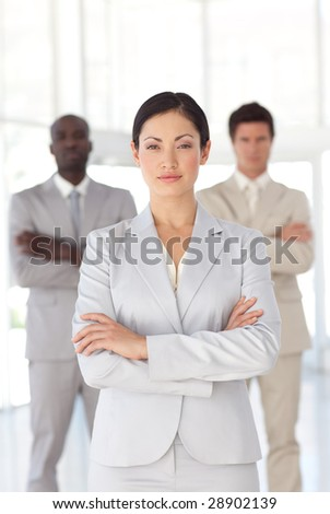 Young attractive Serious Business woman standing in front of a business team - stock photo