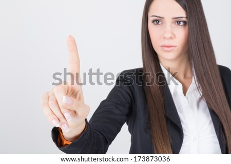 Young attractive serious Caucasian brunette businesswoman pointing with index finger. Copy space available. Future technology and business concepts. - stock photo