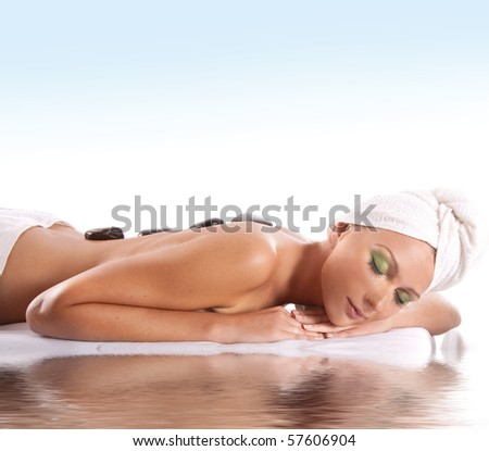 Young attractive sexy blond getting spa treatment isolated on white background - stock photo