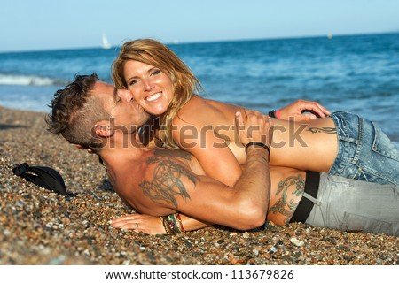 Young attractive sexy couple kissing on pebble beach.