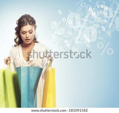 Young attractive shopper girl with shopping bags (discounts and sales concept). - stock photo