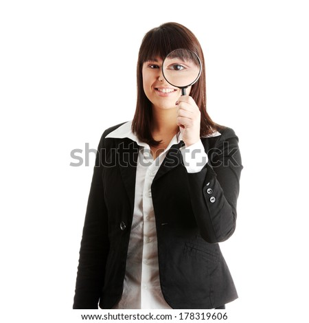 Young attractive smiling business woman looking into a magnifying glass, isolated