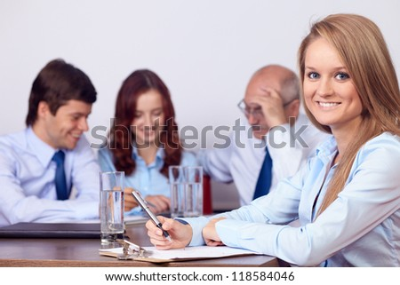 Young attractive smiling businesswoman on a business meeting, background in the office