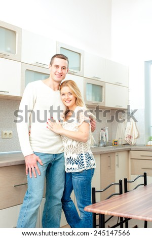 Young attractive smiling couple hugging posing in their kitchen - stock photo