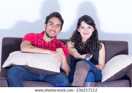 young attractive smiling couple watching movie at home