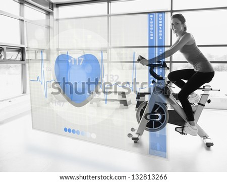 Young attractive smiling girl doing exercise bike with futuristic interface - stock photo