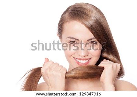 Young attractive smiling woman holding her strong hair and smiling shampoo concept isolated on white - stock photo