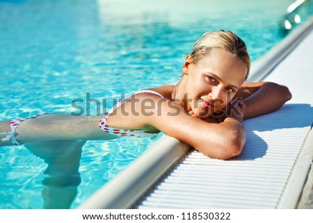 Young attractive smiling woman taking some relax in the beautiful water of the  swimming pool under warm sun - stock photo