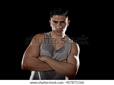 young attractive sport man with big and strong athletic body posing with folded arms wearing sweaty singlet  looking cool and showing attitude isolated on black background - stock photo