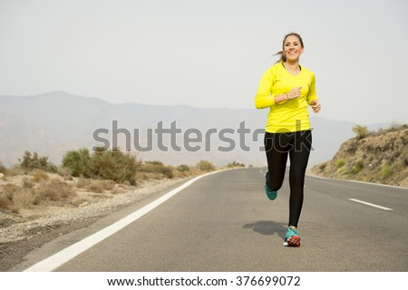young attractive sport woman running on asphalt road with desert mountain landscape background looking happy and healthy in jogging training workout , fitness and wellness concept - stock photo