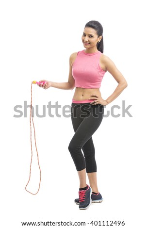 Young attractive sporty girl with skipping rope isolated