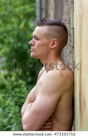 Young, attractive, sporty man leaning against a wall / attractive man / free upper body