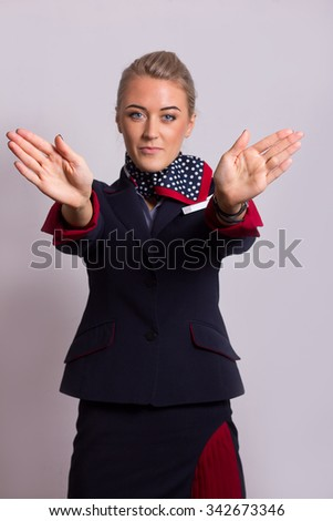 Young attractive stewardess flight attendant performing preflight safety demonstration. Focus on palm. - stock photo