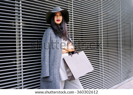 young attractive stylishly-dressed Asian girl posing and holding a blank paper bag with empty space for your text or logo - stock photo