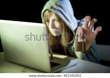 young attractive teen woman wearing hood on looking dark and dangerous hacking laptop computer system holding lock in cybercrime or cyber crime and internet criminal concept  - stock photo