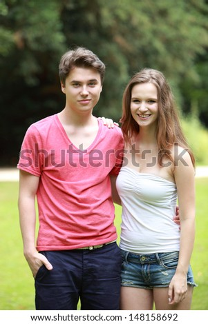 Young attractive teenage boy and girl standing arm in arm in a lush green park - stock photo