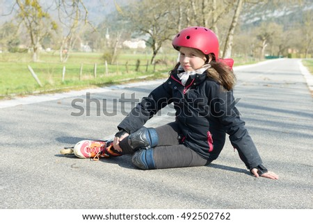 Young attractive teenage skater grimacing in pain after taking a fall on the asphalt