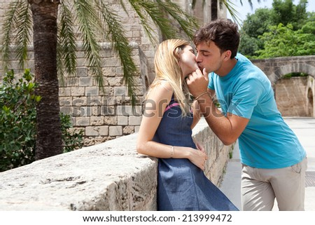 Young attractive tourist couple being close and in love, kissing and hugging with passion and romance while on holiday, visiting a touristic destination city monumental architecture, outdoors. - stock photo