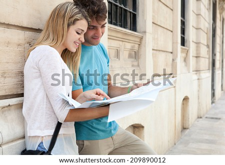 Young attractive tourist couple portrait relaxing in a destination city street with stone buildings, reading a map while on holiday together, outdoors. Travel lifestyle. - stock photo