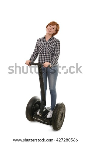 young attractive tourist woman with red hair wearing jeans smiling happy riding electrical segway having fun driving isolated on white background in ecological transport concept - stock photo