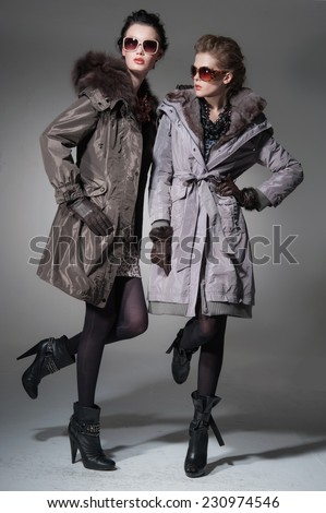 young attractive two girl wearing fur coat on gray background studio shot - stock photo