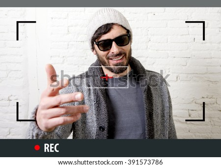 young attractive vlog hipster and trendy style looking man smiling happy  talking to camera posing cool with attitude dressing informal in selfie and internet video blogger recording - stock photo