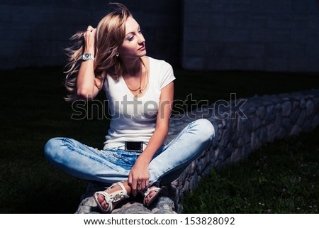 Young attractive woman  a summer day sunset near stone wall sitting on smiling and looking at camera - stock photo