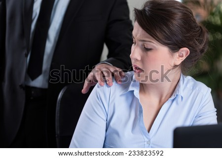 Young attractive woman and workplace harassment - stock photo