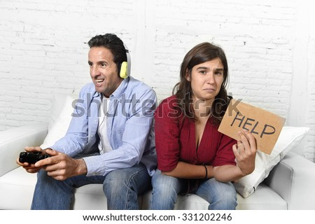 young attractive woman asking for help angry and upset while husband or boyfriend plays videogames ignoring her in technology and gaming addiction concept - stock photo