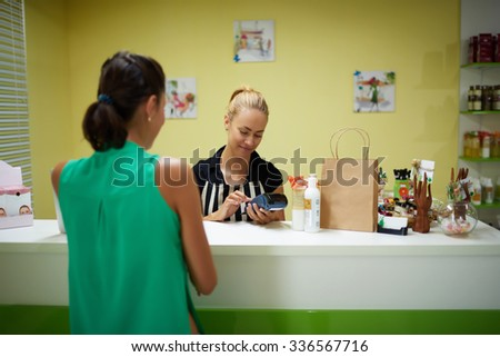 Young attractive woman consultant introduces PIN code in card reader to conduct payment for spa goods, female buyer calculated for purchases while standing in cosmetics store or pharmacy interior  - stock photo